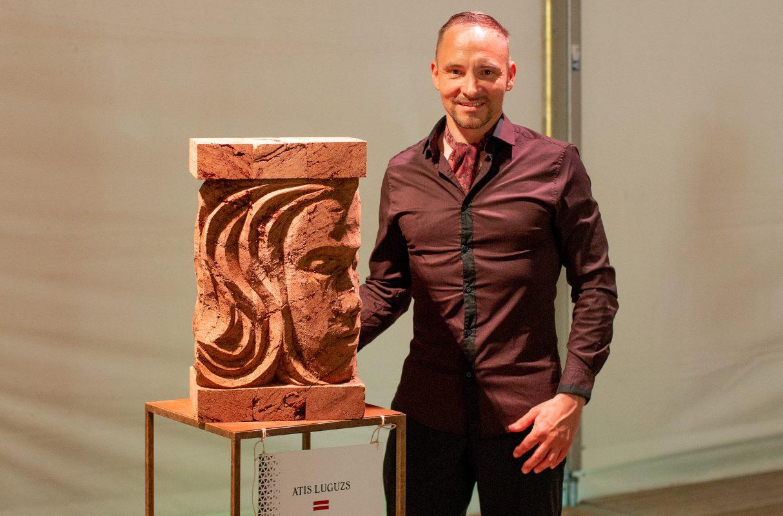 "Artist Atis Luguzs with his peat sculpture ""Portrait of Selma"" at the Peat Sculpture Festival in Eleja, Jelgava county, LATVIA."
